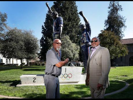 In this October 17, 2018 file photo, John Carlos (left) and Tommie Smith pose for a photo in front of statue that honours their iconic, black-gloved protest at the 1968 Olympic Games, on the campus of San Jose State University in San Jose, California. Smit