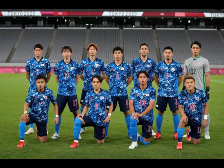 Japan's team players pose for a group photo prior to a men's soccer match between Japan and South Africa at the 2020 Summer Olympics yesterday.