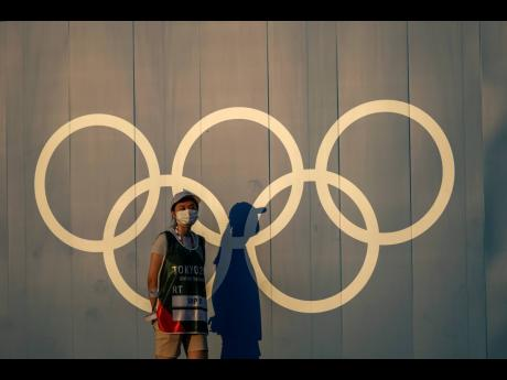 A volunteer walks past the Olympic rings ahead of the 2020 Summer Olympics in Tokyo, Japan, yesterday.