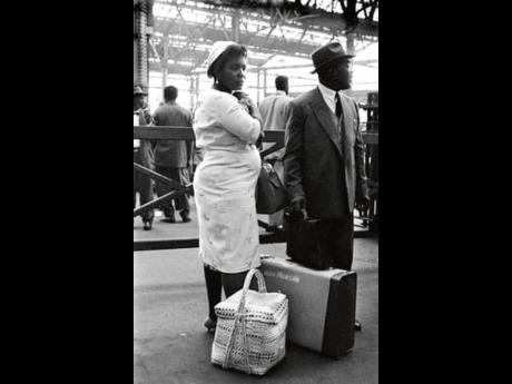 A Caribbean couple on arrival at a UK train station in the 1950s.