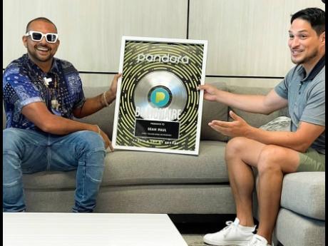 Reggae-dancehall artiste Sean Paul (left) receives his Pandora Billionaires' Club plaque from Diego Herrera, Pandora's head of Caribbean programming.
