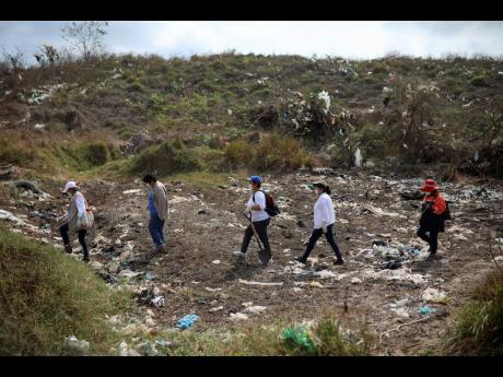 Members of the Solecito Collective, who are seeking their missing loved ones, look for signs of clandestine graves at a municipal dump after an anonymous source sent the group a map suggesting hundreds of bodies were buried in the area, in the port city of