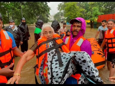 A National Disaster Response Force personnel rescues an elderly woman stranded in floodwaters in Kolhapur, in the western Indian state of Maharashtra yesterday.