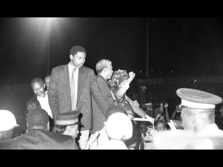 Jamaicans from all over lined up to see the Mandelas. In this photo, Winnie Mandela (right), raises her fist to the crowd as she stands beside husband, Nelson Mandela.