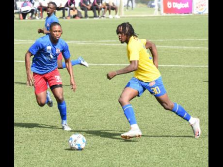 Tevin Scott (right) of Harbour View dribbles past  Dunbeholden's Mark Miller during their Jamaica Premier League match last Saturday. Harbour View won 2-0.