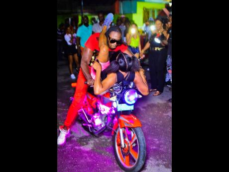 Dancer Expensive performs a stunt with a female on a motorcycle.