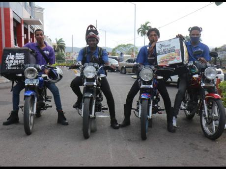 Motorcycle couriers (from left) Romario McCalla, Rocket Delivery Services; Nicholas Linton, supervisor Damian Smith, and Shamar Fray, all of Errand Express, on duty, via online portal ENDS, at a KFC-Pizza Hut site in Montego Bay during lockdown.