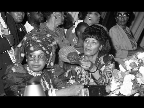 Minister of Labour Welfare and Sports Portia Simpson (right), fans Winnie Mandela during an emotionally-charged event at The Jamaica Pegasus hotel.