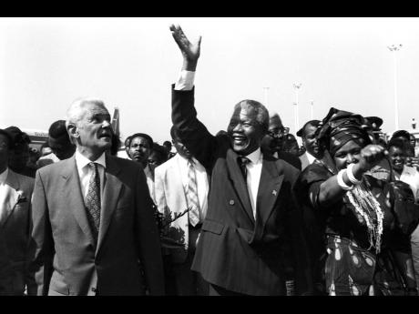 Nelson Mandela, president of the African National Congress of South Africa, waves in appreciation of the tumultuous welcome he received from Jamaicans in the waving gallery and on the tarmac at the Norman Manley Airport on July 24, 1991. Prime Minister Mic