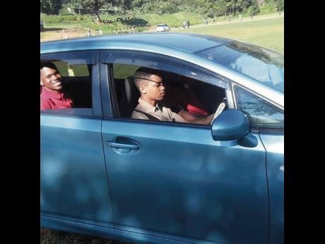 A student from the York Castle High School learning to drive while one of his instructors flashes a smile.