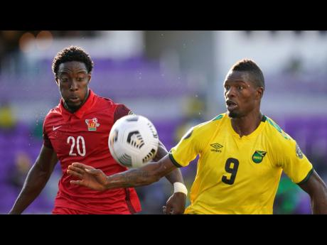 Jamaica's forward Corey Burke (9) challenges for the ball with Guadeloupe defender Stevenson Casimir (20) during the first half of their CONCACAF Gold Cup Group C soccer match on Friday, July 16, in Orlando, Florida.
