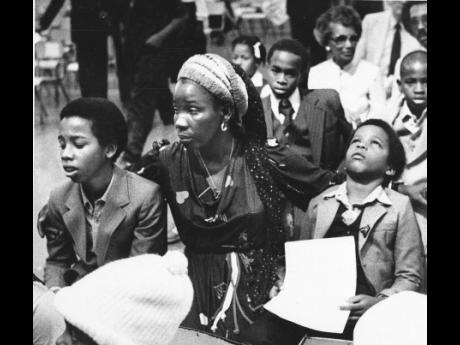 Rita Marley, widow of reggae superstar Bob Marley, and her two sons, Ziggy (left) and Stephen, attend Bob Marley's funeral in Kingston, May 21, 1981.