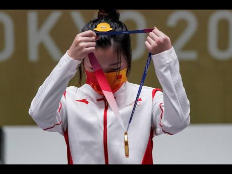 Yang Qian of China puts on her gold medal after the women's 10-metre air rifle at the Asaka Shooting Range, during the 2020 Summer Olympics in Tokyo, Japan, yesterday.