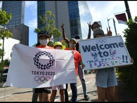 Japanese nationals display welcome signs in close proximity to the Olympic Village in Tokyo, Japan, on Friday, July 23, 2021.