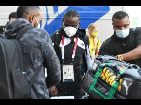 Sprinter Jevaughn Minzie (centre) is among the contingent of Jamaican athletes and coaches that arrived at the Olympic Village on Friday, July 23, 2021.