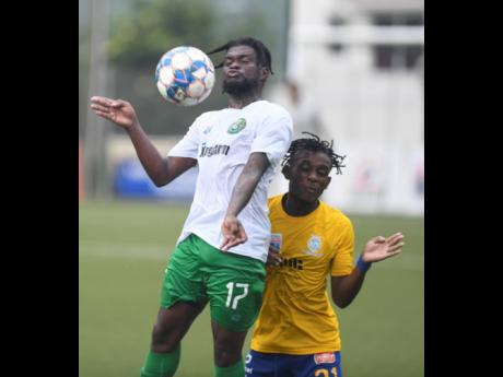 Vere United's Ricardo Dennis (front) jumps to control the ball as he is challenged from behind by Harbour View FC's Odorland Harding, during their Jamaica Premier League football match at Captain Burrell Centre of Excellence, UWI, Mona, yesterday. Ver