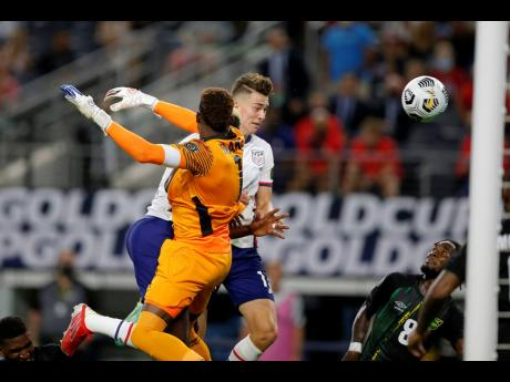 Jamaica goalkeeper Andre Blake (front) is unable to stop a header by United States forward Matthew Hoppe (centre right) breaching his goal as defender Oniel Fisher looks on late in the second half of their Concacaf Gold Cup quarter-final match in Arlington