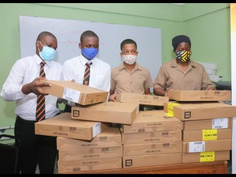 From left: Layandre' Akoto, Damoyie Sterling, Tyreke Ellis and Jahlani Ustanny adjust the still-packaged Dell laptop computers that they were presented with during a handing-over ceremony at the school in Montego Bay on July 22, where 115 laptops were do