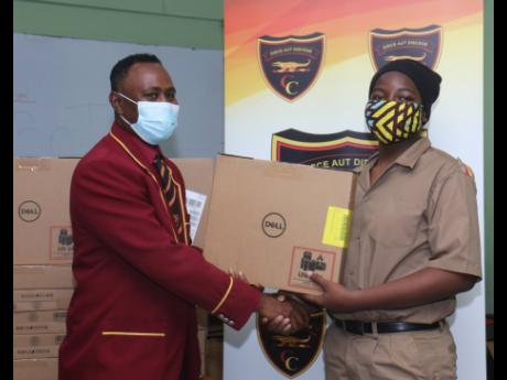 Jahlani Ustanny (right), a grade nine student of Cornwall College receives one of 115 Dell laptop computers from Dr Richard Meggo, president of the Cornwall College Alumni Association's Montego Bay chapter, during a ceremony to hand over the devices to t