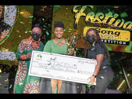 Minister of Culture, Gender, Entertainment and Sport Olivia 'Babsy' Grange (left), and Digicel Brand Marketing Manager Reshima Kelly-Williams (right) hand over the grand prize of $3 million to an overjoyed Stacious, winner of the 2021 Jamaica Festival