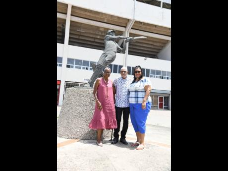 The brithday boy, Headley George 'Dellmar' Samuels (centre), is sandwiched by two of his leading ladies — wife, Carol and daughter, Karyn Quallo.
