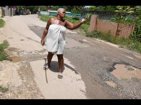 Arlene Melbourne is visibly upset as she points out the poor condition of the August Town Road in Bog Walk, St Catherine on July 21.