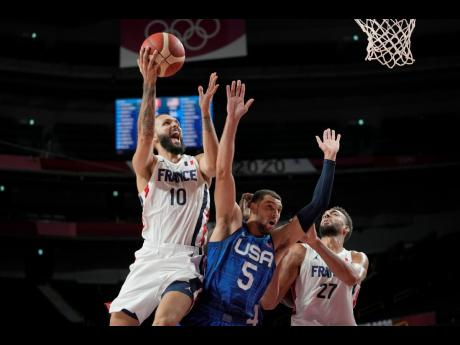 France's Evan Fournier (left) shoots over United States of America guard Zachary Lavine (centre) during a men's basketball preliminary-round game at the Tokyo Olympic Games in Saitama, Japan, yesterday.