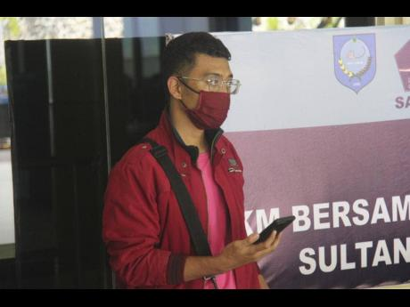 A man who used a fake identity arrives at the Sultan Babullah Airport in Ternate, Indonesia. The man with the coronavirus boarded a domestic flight disguised as his wife, wearing a niqab covering his face and carrying fake IDs and a negative PCR test resul