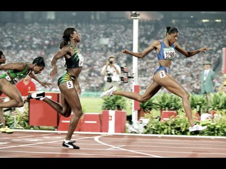 Gold medalist Marie-José Pérec of France (right) crosses the finish line ahead of silver medalist Merlene Ottey of Jamaica (centre) and bronze medalist Mary Onyali of Nigeria during the Women's 200m final at the 1996 Summer Olympic Games in Atlanta, Ge