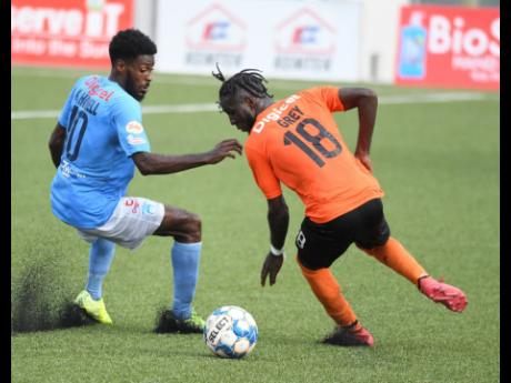 Tivoli Gardens' Devroy Grey (right) turns away from his marker, Waterhouse's Denardo Thomas, during their Jamaica Premier League game at the UWI/JFF Captain Horace Burrell Centre of Excellence on Monday.