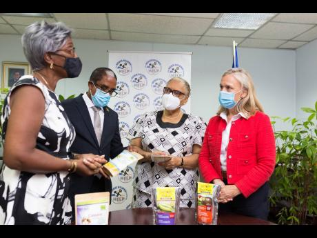 President of the Jeffrey Town Farmers Association, Ivy Gordon (left), shares some of the association's products with (from second left) State Minister in the Ministry of Industry, Investment & Commerce, Dr Norman Dunn; Chief Executive Officer of the Jama