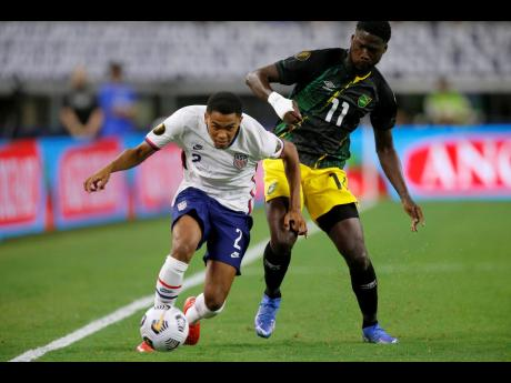 United States defender Reggie Cannon gets past Jamaica forward Shamar Nicholson (right) during their Gold Cup quarterfinals match in Arlington, Texas, on Sunday.