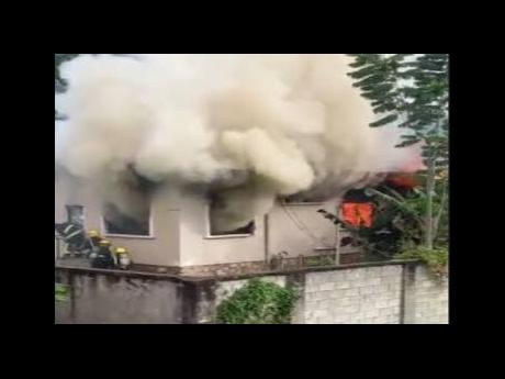 Smoke billows from the house where three children lost their lives in a Monday morning blaze in Maraval, outside Port-of-Spain, Trinidad.