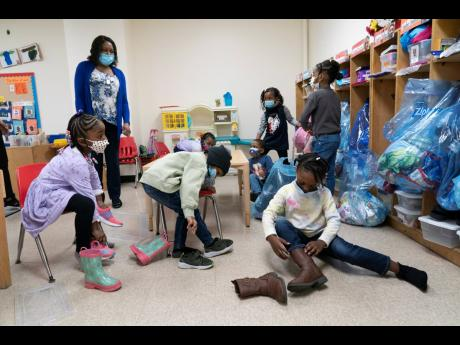 In this Wednesday, March 24, photo, Pre-K students arrive for the school day at Phyl's Academy in the Brooklyn borough of New York. New York City will require all of its municipal workers – including teachers and police officers – to get coronavirus