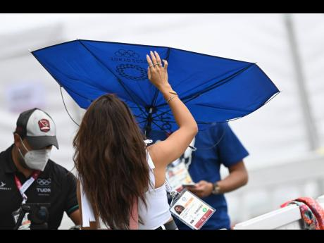 A gust of wind makes light work of this lady's umbrella at the warm-up track.