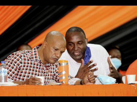 People's National Party General Secretary Dayton Campbell (right) has dialogue with Peter Bunting, chairman of the party's Manchester Central constituency conference, at Manchester High School on Saturday.