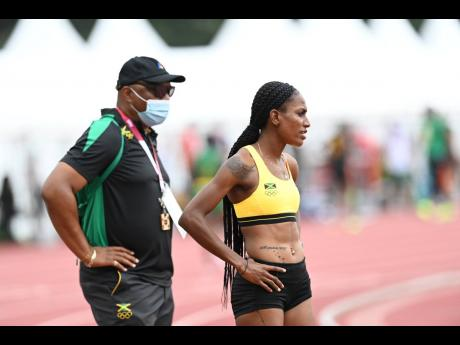 Akimbo on the double: Head coach Maurice Wilson and 400m hurdler Ronda Whyte are seen at the warm-up track at the Tokyo Olympic Stadium on Monday.