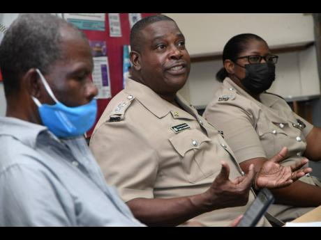 Senior Superintendent of Police Gary McKenzie (centre), head of the Police Safety and Traffic Enforcement Branch, addresses a meeting of the Transport Operators Development Sustainable Services (TODSS) at Half-Way Tree Primary School on Sunday. He is flank
