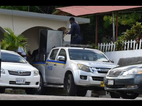 Policemen remove furniture from the Teamwork Retreat Centre in St James on Friday, reportedly en route to the nearby Freeport Police Station for storage. Dozens of policemen assigned to the zone of special operations in the parish were scrambling to find a