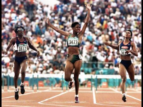 Deon Hemmings-McCatty (centre) celebrates after winning the 400m hurdles ahead of Americans Kim Batten (left) and Tonja Buford-Bailey who were second and third respectively at the Atlanta Olympic Games on Wednesday, August 31, 1996.