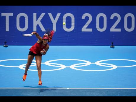 Naomi Osaka, of Japan, serves to Viktorija Golubic, of Switzerland, during the second round of the tennis competition at the 2020 Summer Olympics in Tokyo, Japan on Monday.