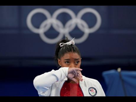 Simone Biles, of the United States, watches gymnasts perform after an apparent injury, at the 2020 Summer Olympics in Tokyo, Japan on Tuesday.