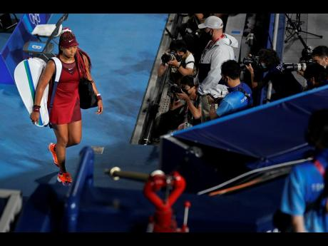 Naomi Osaka, of Japan, leaves centre court after being defeated by Marketa Vondrousova, of the Czech Republic, during the third round of the tennis competition at the 2020 Summer Olympics in Tokyo, Japan on Tuesday.