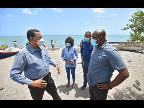 Minister of State in the Ministry of Local Government and Rural Development, Homer Davis (left), in conversation with Member of Parliament for South West Clarendon, Lothan Cousins (right), while touring a section of the community of Banks in the parish on