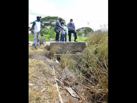 Minister of State in the Ministry of Local Government and Rural Development, Homer Davis (right), and Member of Parliament for South West Clarendon, Lothan Cousins (left), point to a blocked drain in the community of Banks during a tour on July 22. Looking
