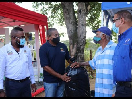 Minister of Agriculture and Fisheries Floyd Green (second left), makes symbolic presentation of 300 50-lb bags of silage to Martin Golaub (second right), member of the St Elizabeth Dairy Development Co-operative during a handover ceremony at Island Dairies