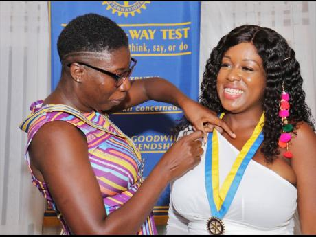 Amber-Gail Grandison, the newly installed president of the Rotary Club of Montego Bay, gets her presidential pin attached by Cortia Shepherd during the annual installation ceremony at Day-O Plantation Restaurant & Bar on Saturday evening.