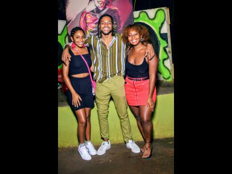 With 'Entertainer' as his backdrop, the digital artist behind the augmented-reality dancehall exhibit, Bonito 'Don Dada' Thompson, is joined by beauties Alex Rodriques (left) and Morgan Phillips.
