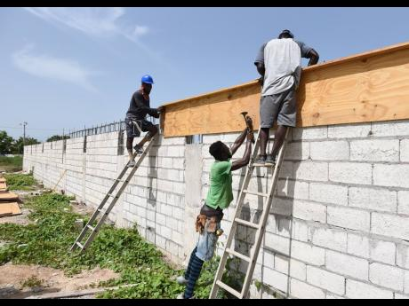 From left: Workmen Akeem Henry, Dewight Collings, and Melvin Tulloch construct a perimeter wall at an open lot in Gordon Pen, St Catherine, that will serve as a new sports complex in honour of West Indies Women's cricket team captain Stafanie Taylor and