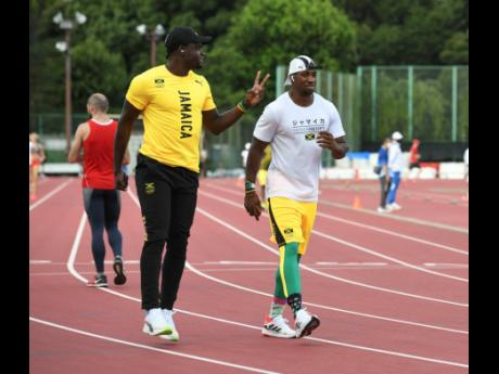 Jevaughn Minzie (left) and Yohan Blake exercise on the warm-up track of the Tokyo Olympic Stadium on Tuesday.